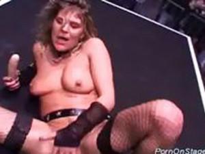 Une fille en bas résille se masturbe sur scène
